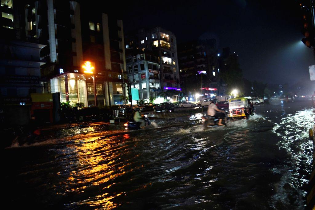 Patna :  Commuters wade through the waterlogged Gandhi Maidan Road after heavy rain, during the monsoon season, in Patna on Monday  14 June 2021.