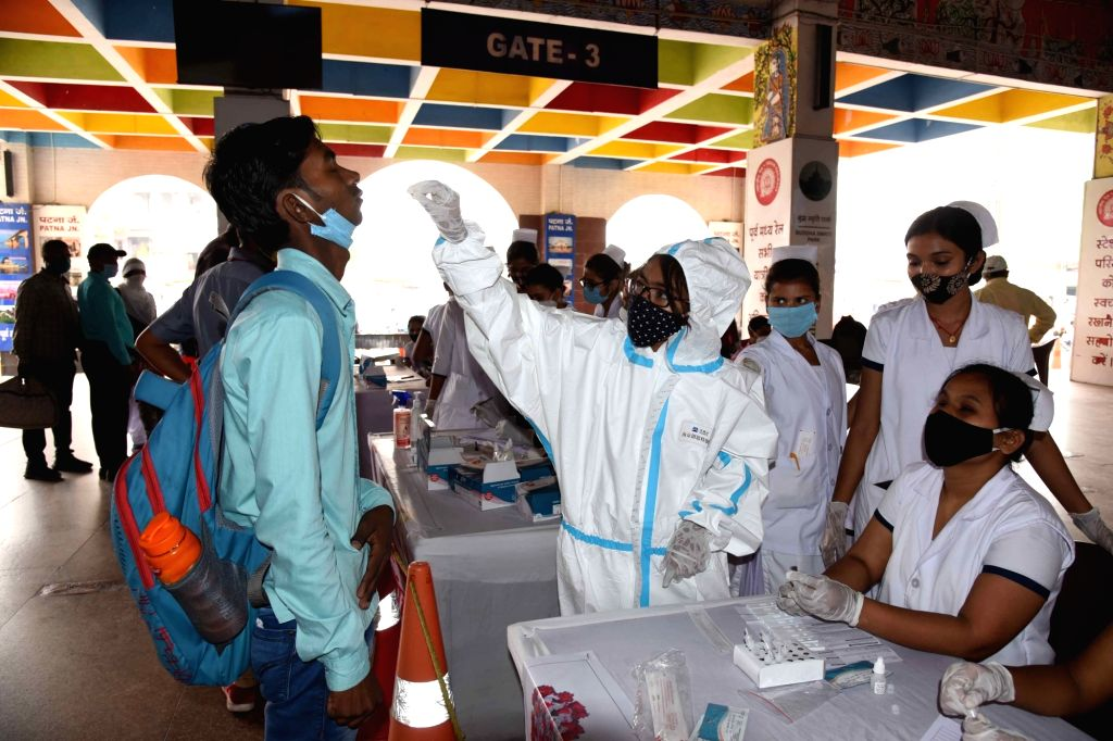 Patna: Health worker takes swab sample of a passenger at Patna junction arrive from Mumbai via special train, as coronavirus cases spike across the country, in Patna on Friday, April 9, 2021,(photo:AFTAB ALAM SIDDIQUI/IANS)