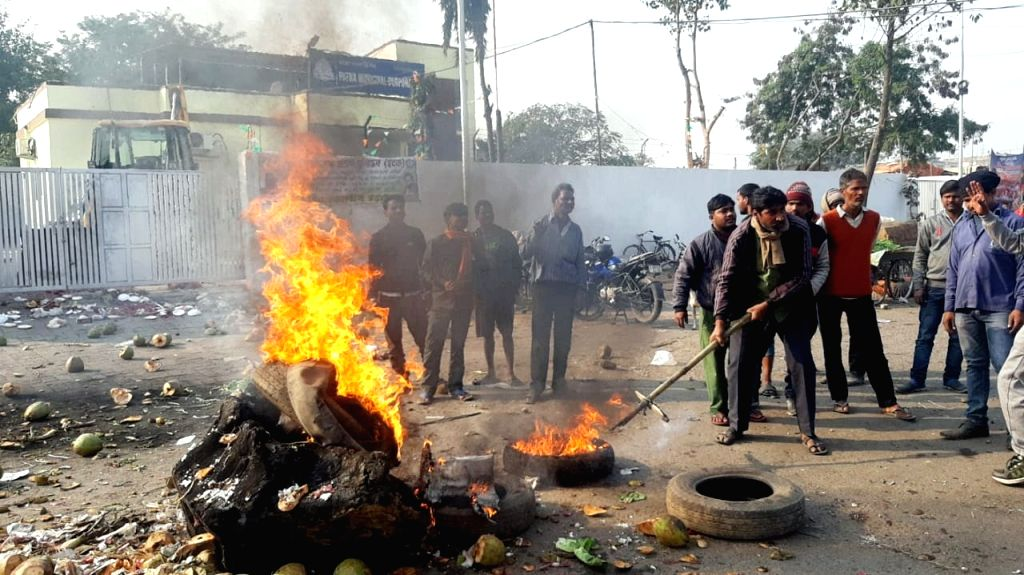 Patna Municipal Corporation (PMC) workers burn tyres as they protest during their strike over their various demands, in Patna on Feb 5, 2020.