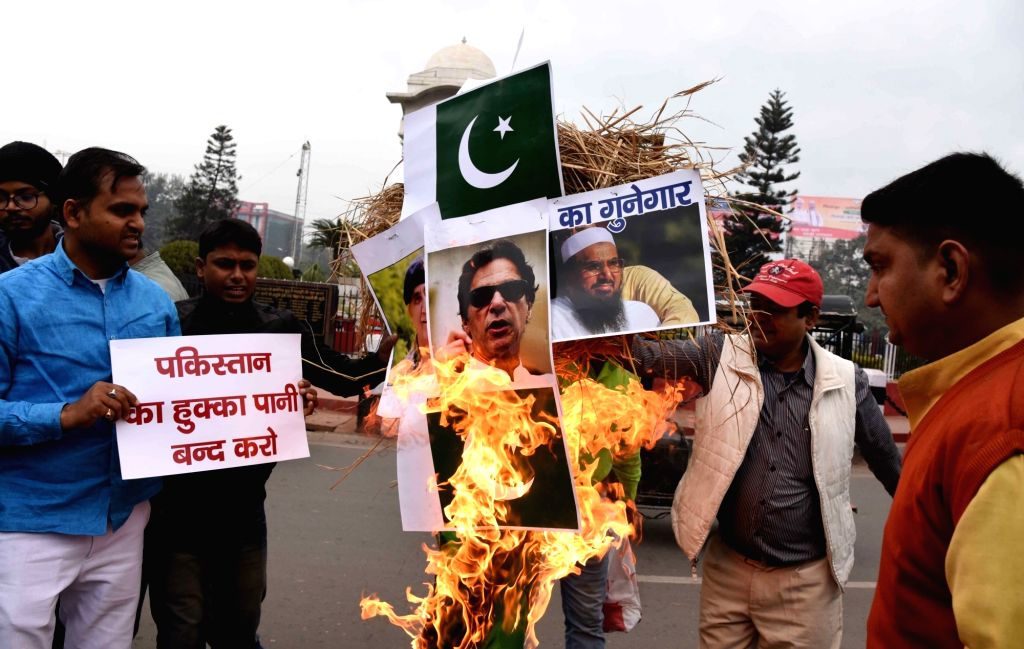 Patna: People burn pictures of Pakistan Prime Minister Imran Khan, Jamaat-ud-Dawa chief Hafiz Saeed and Pakistan flag as they protest against suicide attack on a CRPF bus in Jammu and Kashmir's Pulwama district in which atleast 45 soldiers lost their - Imran Khan