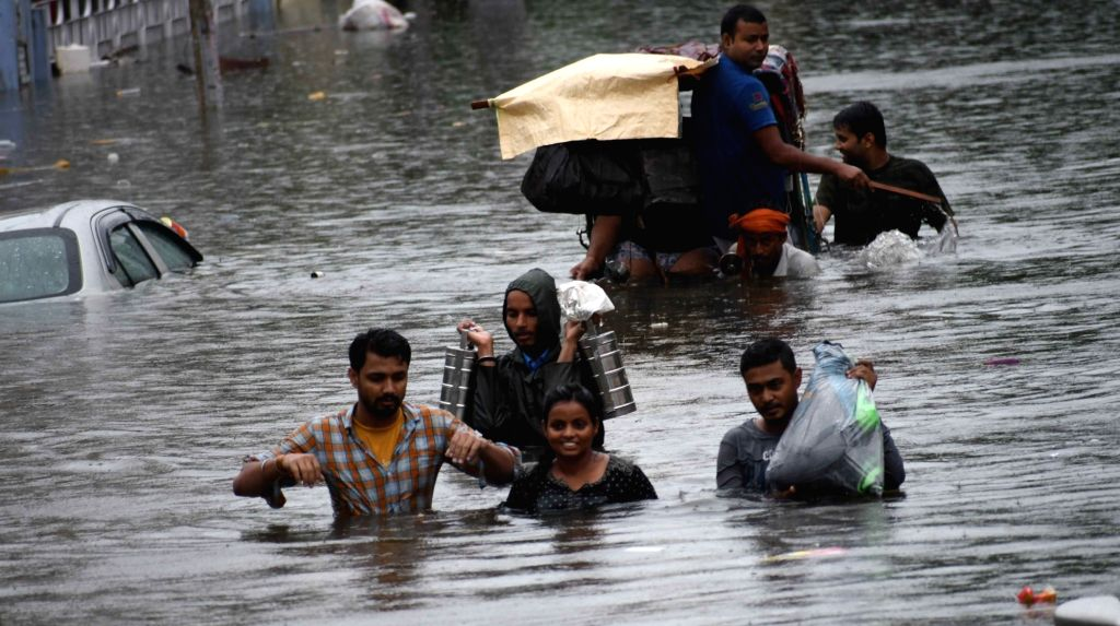 Patna: People wade through waist-deep waterlogged streets to buy essentials, as the locality remains flooded in Patna, on 29 Sep, 2019. (Photo: IANS)