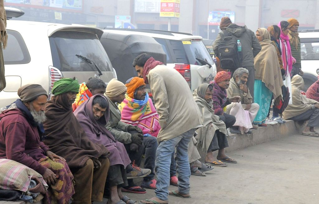 Patna: People wearing warm clothes to beat the cold, outside Patna Railway station. (Photo: IANS)