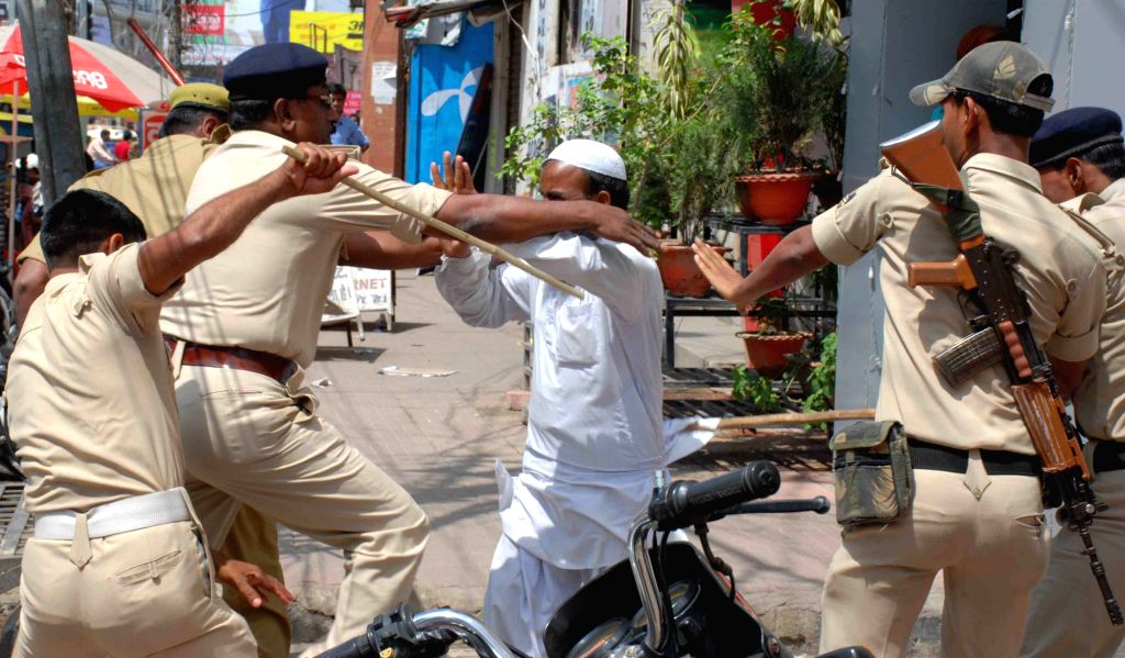 Policemen take away a TET qualified candidate staging a demonstration in Patna, on April 8, 2015.