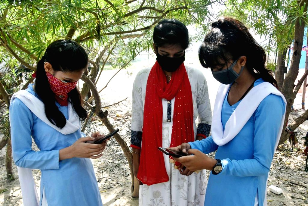 Patna: Students check their results on their smartphones after the Bihar School Education Board (BSEB) declared Class 10 results, in Patna on May 26, 2020. (Photo: IANS)