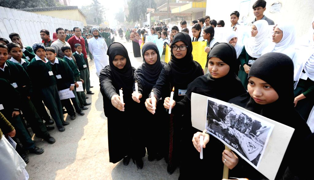 Students participate in a candlelight vigil to condemn Tuesday's attack on the Army Public School in Peshawar, Pakistan, that claimed 148 lives mostly those of children, in Patna on Dec 18, ...