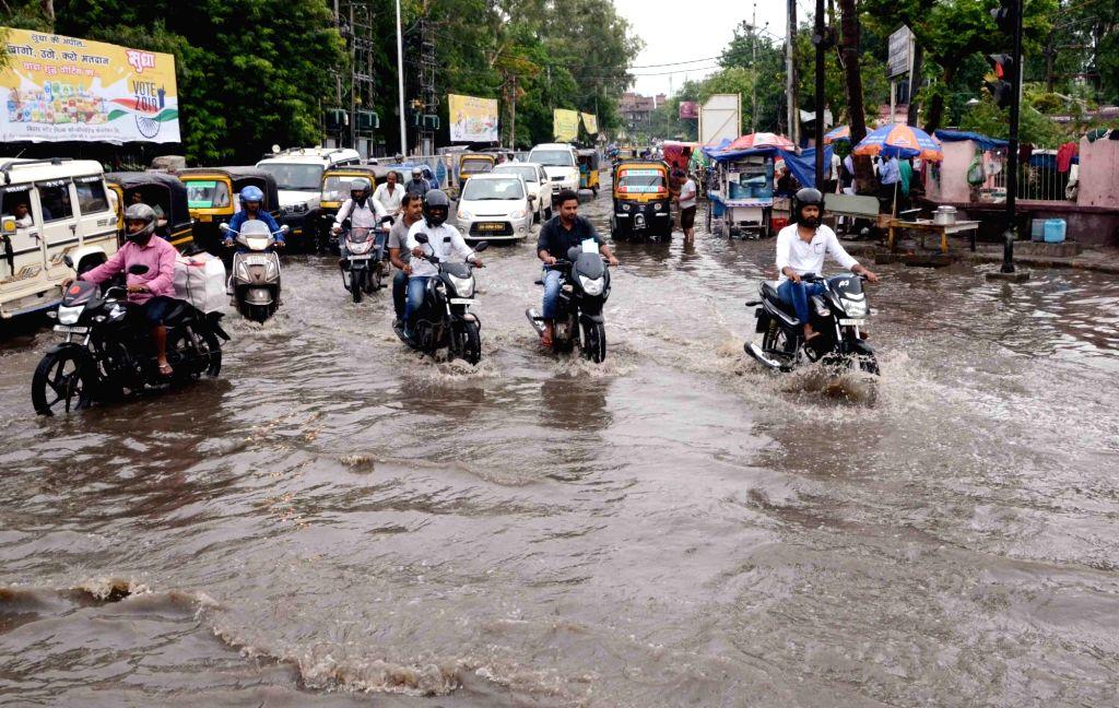 Patna: Vehicles struggle through a waterlogged street in Patna, on July 8, 2019. (Photo: IANS)