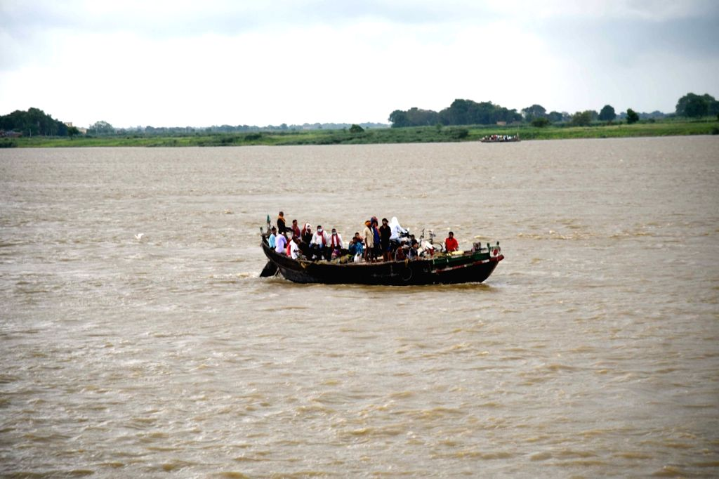 Patna: Villagers sail through the Ganga river on a boat during the total lockdown imposed in the wake of the rising cases of coronavirus, in Patna, on July 21, 2020. (Photo: IANS)