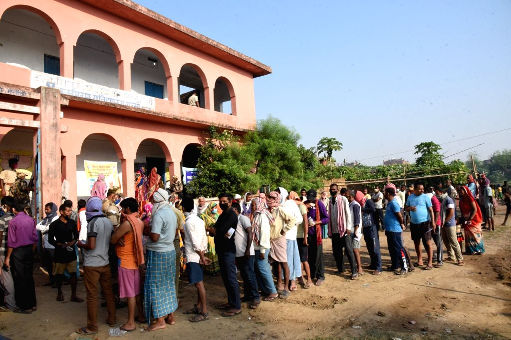Patna: Voters queue up to cast their votes for the first phase of Bihar Assembly elections, at a polling station in Patna on Oct 28, 2020. (Photo: IANS)