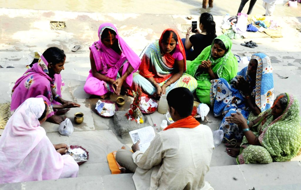 """Patna: Women perform rituals on the banks of Ganga river during """"Jivitputrika"""" festival - observed by mothers for the well being of their children - in Patna on Oct 2, 2018. (Photo: IANS)"""