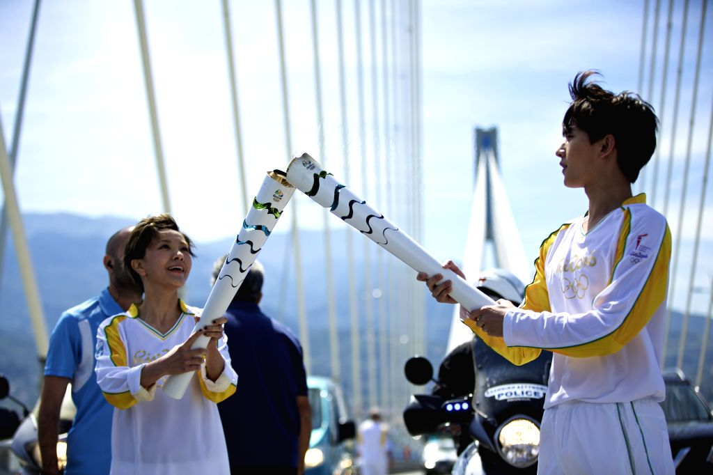 PATRA, April 22, 2016 - Olympic flame torchbearer, Chinese actor Yang Yang (R) passes the flame to Chinese actress Amber Kuo during the torch relay of the Rio Olympic Games on Rio-Antirrio Bridge of ... - Yang Yang