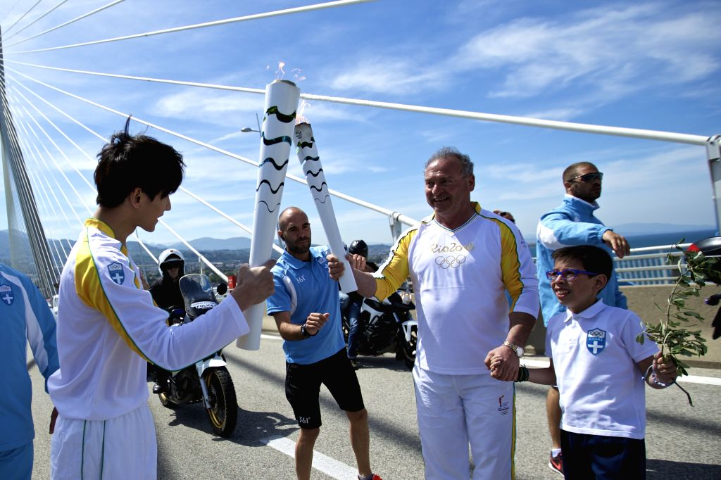 PATRA, April 22, 2016 - Olympic flame torchbearer, Greek former cross-country skier Vasilis Katsoras, passes the flame to Chinese actor Yang Yang during the torch relay of the Rio Olympic Games on ... - Yang Yang