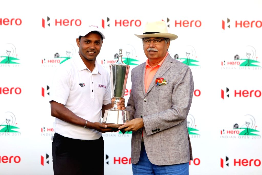 Pawan Munjal, CMD of Hero MotoCorp, handing over the winner's trophy to SSP Chawrasia who successfully defended his Hero Indian Open title in Gurugram on March 12, 2017.
