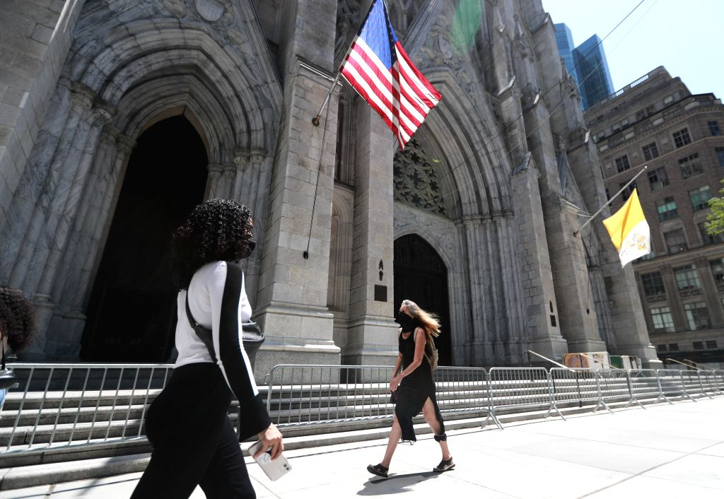 Pedestrians walk past St. Patrick's Cathedral on Fifth Avenue in New York, the United States, July 4, 2020. The number of COVID-19 cases in the United States topped ...