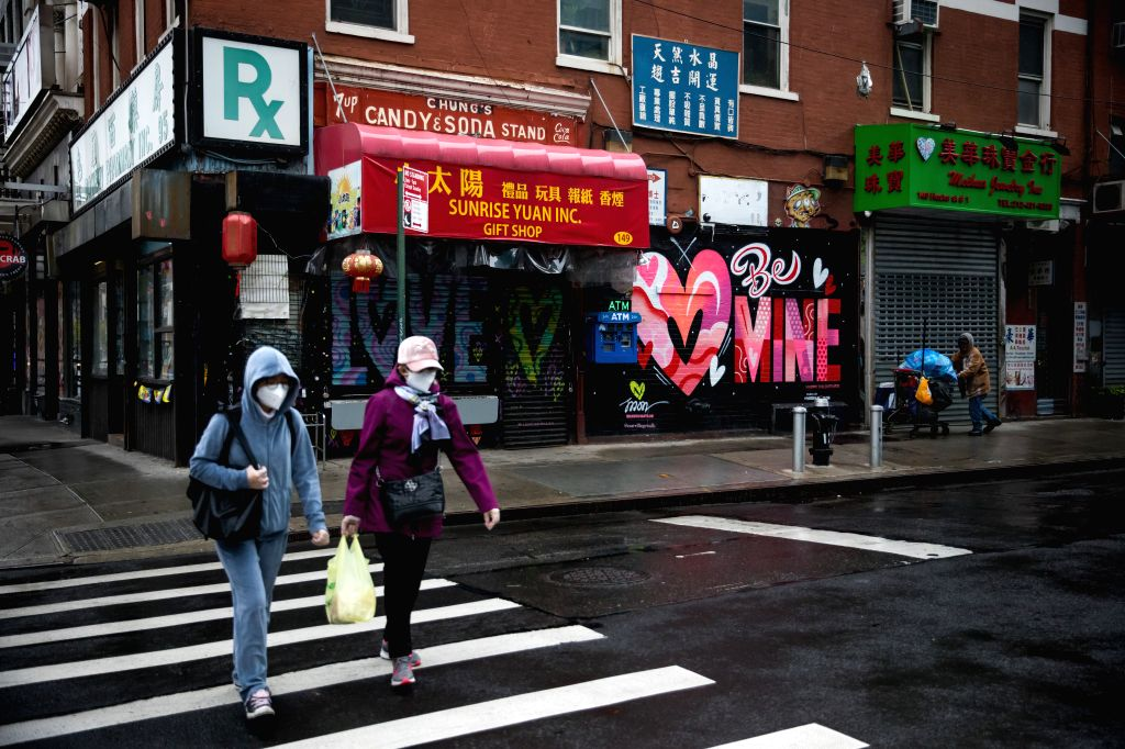 Pedestrians wearing face masks walk across a street in New York, the United States, on May 8, 2020. New data showed that U.S. employers cut a staggering 20.5 million ...