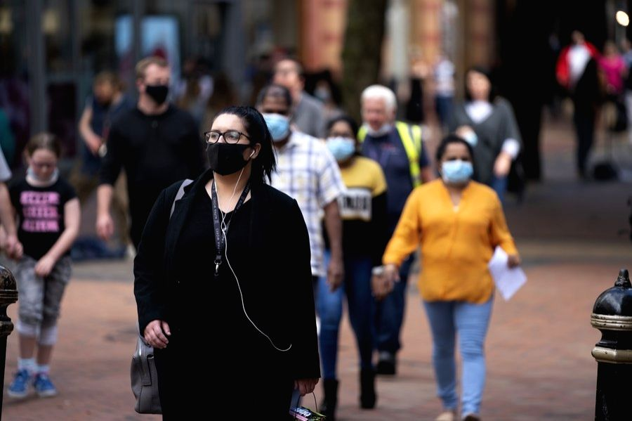 Pedestrians wearing face masks walk in the city centre of Birmingham, Britain, Aug. 24, 2020.