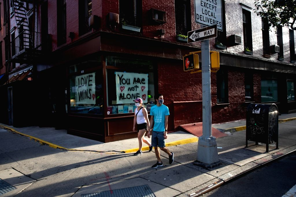 Pedestrians wearing face masks walk on the street during the COVID-19 pandemic in New York, the United States, on Sept. 13, 2020. The total number of COVID-19 ...