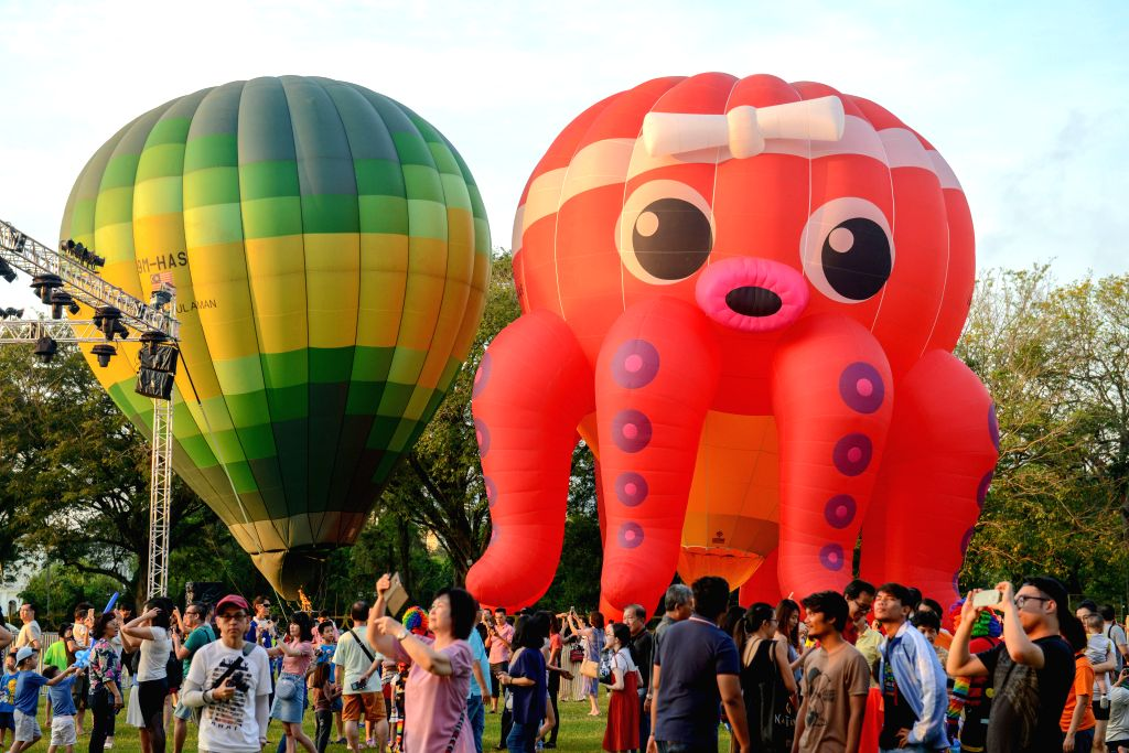 PENANG, Feb. 10, 2019 - People visit the Penang Hot Air Balloon Fiesta in Penang, Malaysia, Feb. 10, 2019. Numerous hot air balloons by international and local balloonists are displayed over the ...