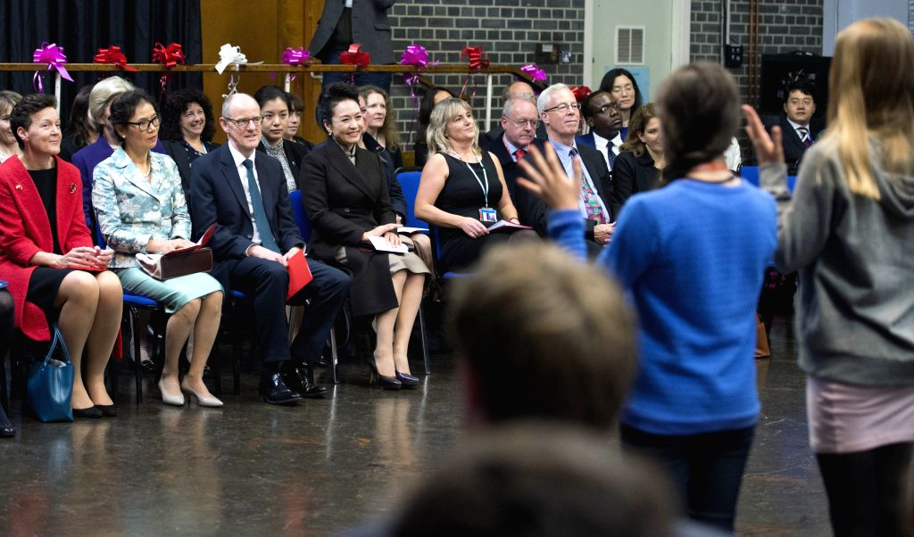 Peng Liyuan (4th L, front row), Chinese President Xi Jinping's wife, watches students' performance during a visit to Fortismere School in London, Britain, Oct. 21, ...