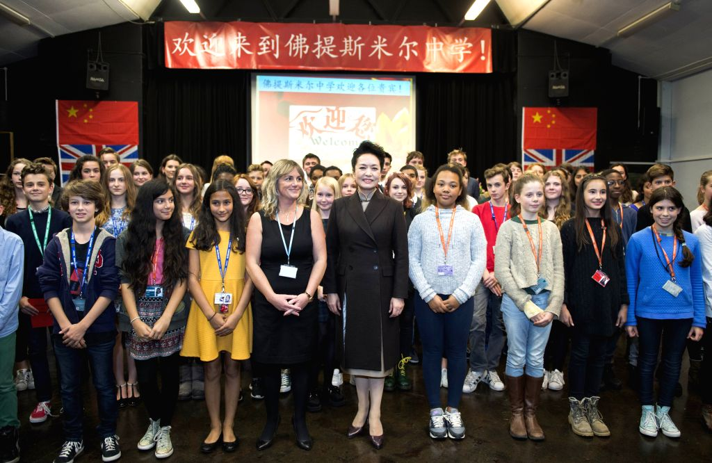 Peng Liyuan (C, front), Chinese President Xi Jinping's wife, poses for a group photo with students during a visit to Fortismere School in London, Britain, Oct. 21, ...