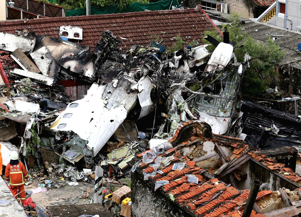 Photo taken on July 24, 2014 shows the accident site after a Taiwan plane  smashed into residential buildings following a failed emergency landing in the outlying ...