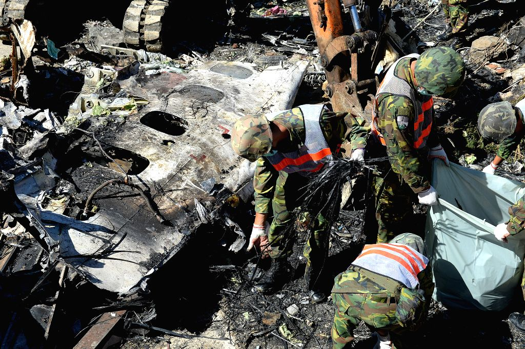 Rescuers work at the crash site of TransAsia Airways Flight GE 222 on Chinese Taiwan's Penghu Island, July 25, 2014. The rescue and on-the-spot survey on the air ...