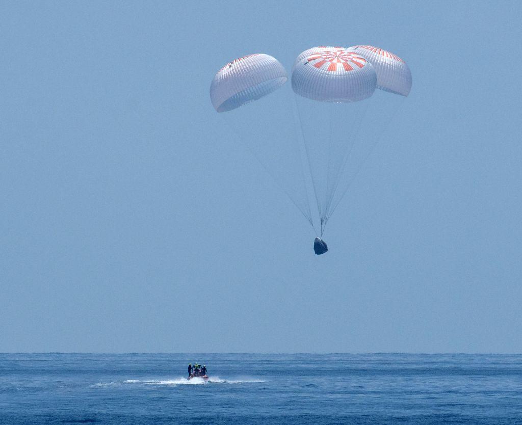 """Pensacola (U.S.), Aug. 2, 2020 The SpaceX Crew Dragon """"Endeavour"""" spacecraft parachutes to a splashdown off the coast of Pensacola, Florida, the United States, on Aug. 2, 2020. ..."""