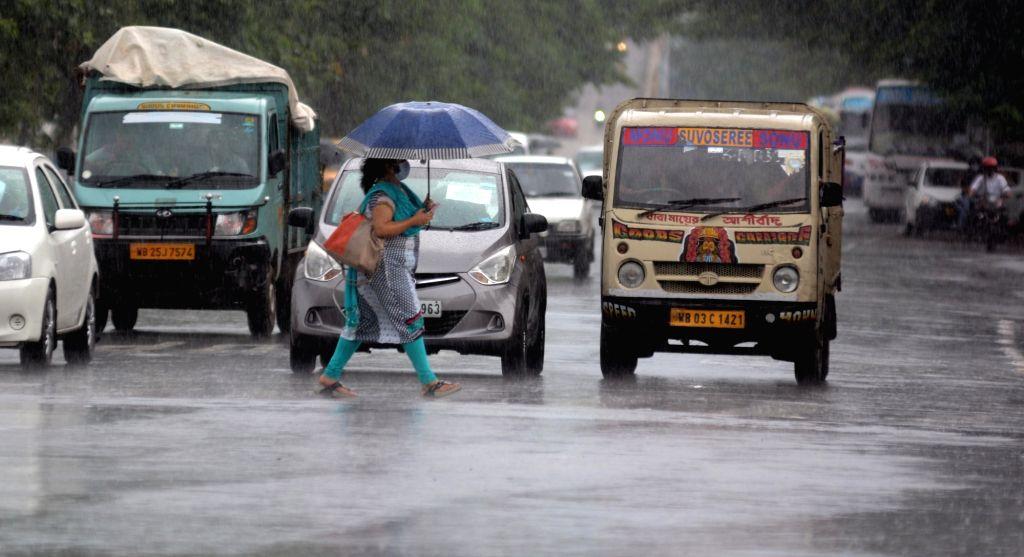 People are crossing the road in the rain in Kolkata in Kolkata on Friday 11 June, 2021.
