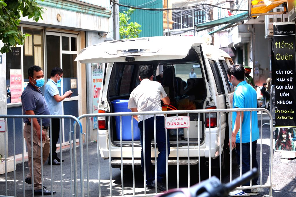 People are seen in a locked-down alley, where a newly confirmed patient with COVID-19 lives, in Hanoi, Vietnam, on July 29, 2020. Vietnam reported 12 new cases of ...