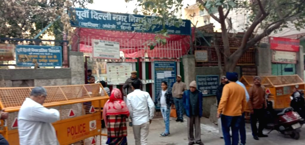 People arrive to cast their votes for Delhi Assembly elections 2020 amid tight security, at a polling station at East Azad Nagar on Feb 8, 2020.