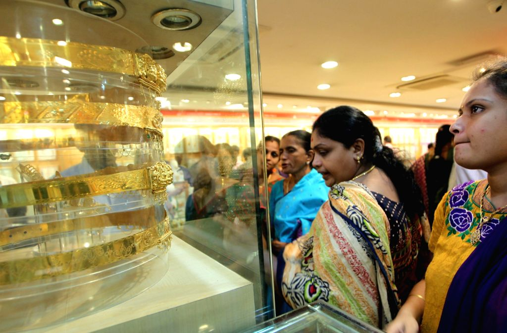 People at a jewellery showroom in Chennai on August 16, 2013. The prices of the yellow metal has been increasing in the last week and it stood at Rs 2,904 per gram in Chennai. (Photo::: IANS)