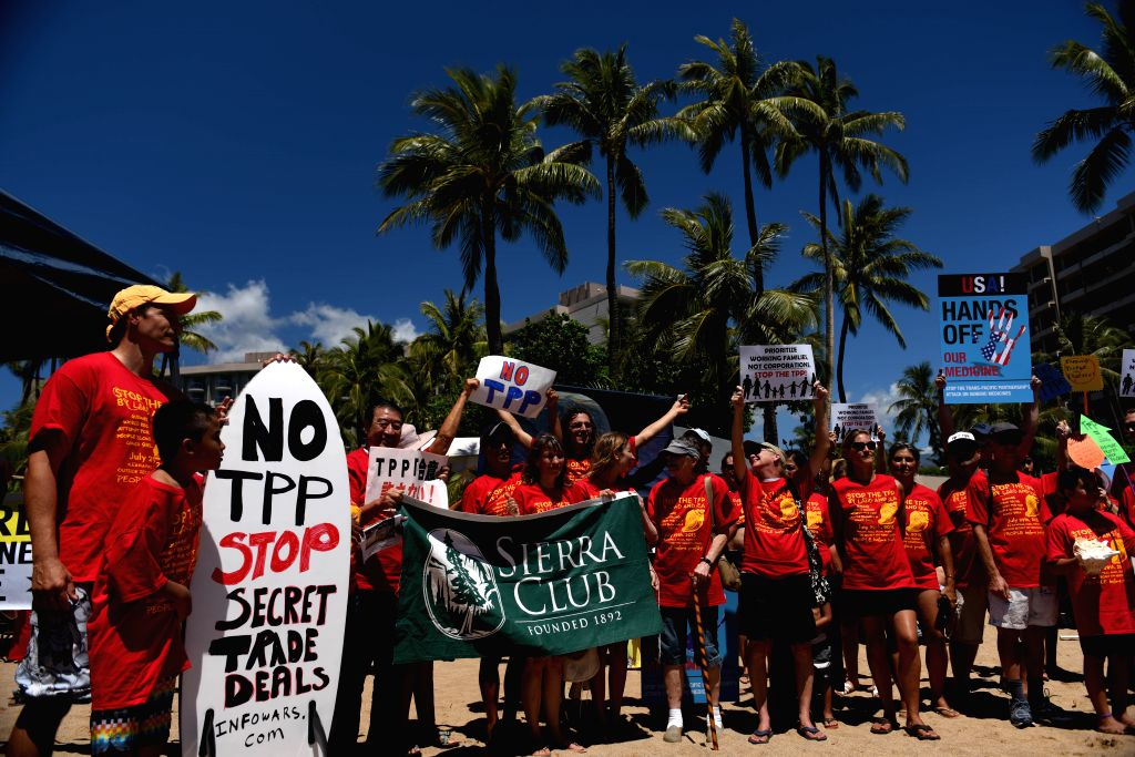 People attend a rally protesting the Trans-Pacific Partnership (TPP) in Maui, Hawaii, the United States, July 29, 2015. Hundreds of local residents and representatives ...
