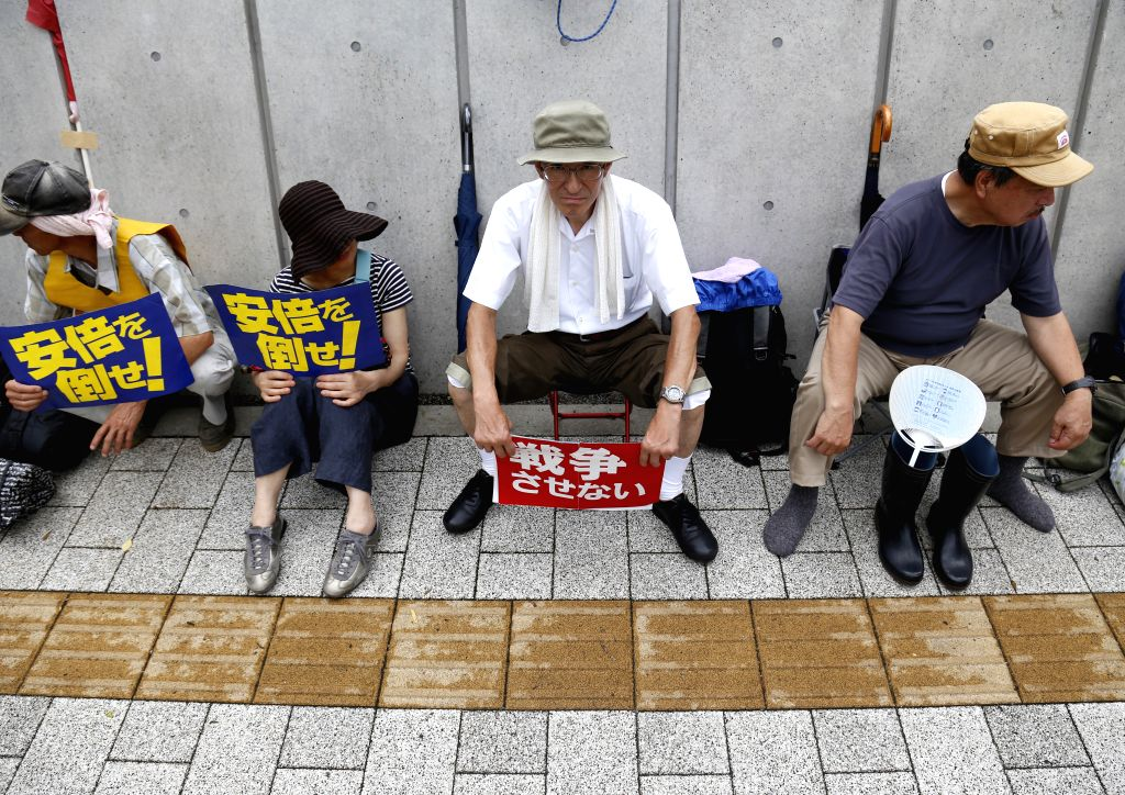 People attend a sit-in protest against the security bills near the parliament building in Tokyo, Japan, July 16, 2015. Japan's ruling coalition led by Prime Minister ... - Shinzo Abe