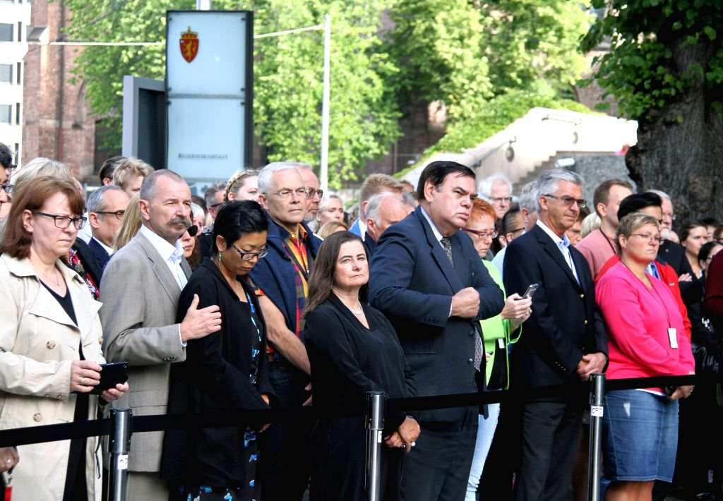 People attend a wreath-laying ceremony in front of the damaged government building which used to house the office of Norway's prime minister, in Oslo, Norway, July 22, ... - Erna Solberg
