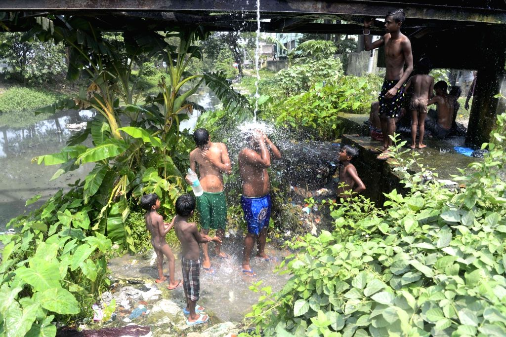 People bath in open on a hot day in Kolkata on May 21, 2017.