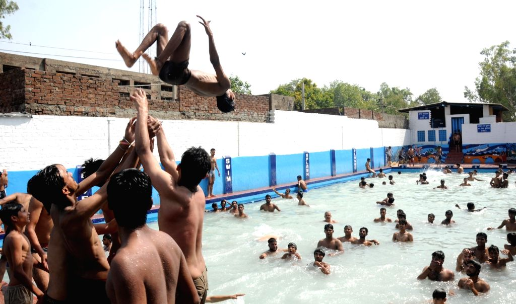 People beat the heat in a swimming pool on a hot day in Amritsar on June 6, 2016.