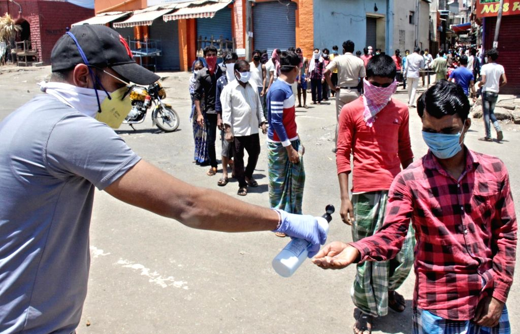 People being offered hand sanitiser as they queue up to collect food during free food distribution on Day 6 of the 21-day countrywide lockdown imposed to contain the spread of novel ...