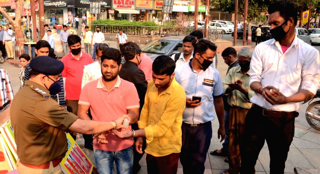 People being provided with hand rub sanitiser during an awareness drive being conducted by the police to alert people on measures they should take to contain the spread of COVID-19, in Noida ...