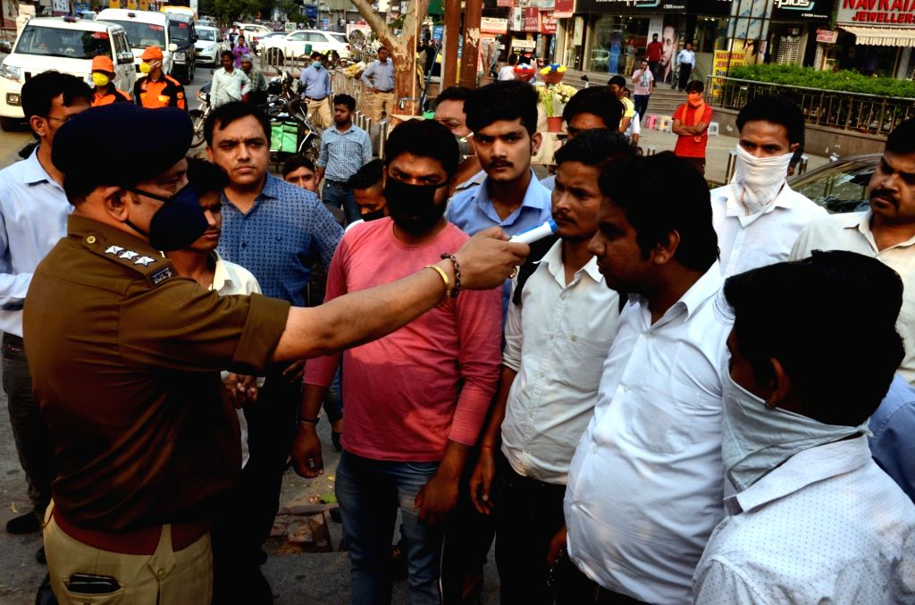 People being screened for COVID-19 during an awareness drive being conducted by the police to alert people on measures they should take to contain the spread of COVID-19, in Noida on March 21, ...