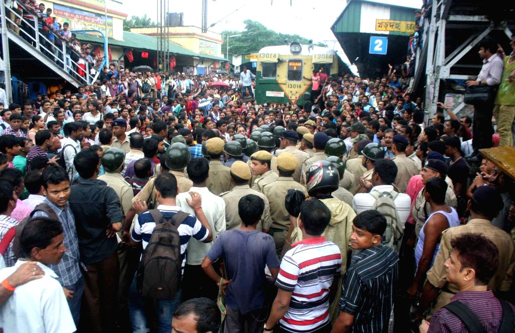 People block rail services at Khardah station in North 24 Parganas of West Bengal on Aug 17, 2015. The protest started after Railways decided to convert four EMU coaches of ladies special, ...