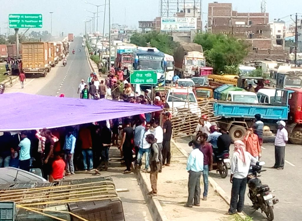 People block vehicular movement as they stage a demonstration against water accumulation on Bypass Road near Krishna Niketan, in Patna on Oct 9, 2019.