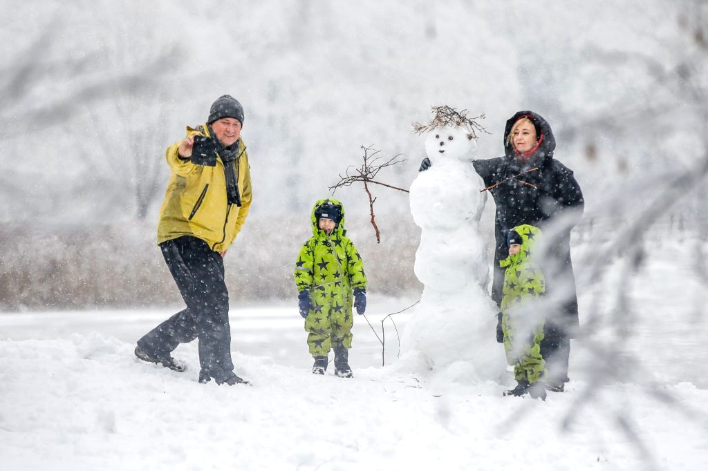 People build a snowman in Moscow, Russia, Jan. 11, 2020.