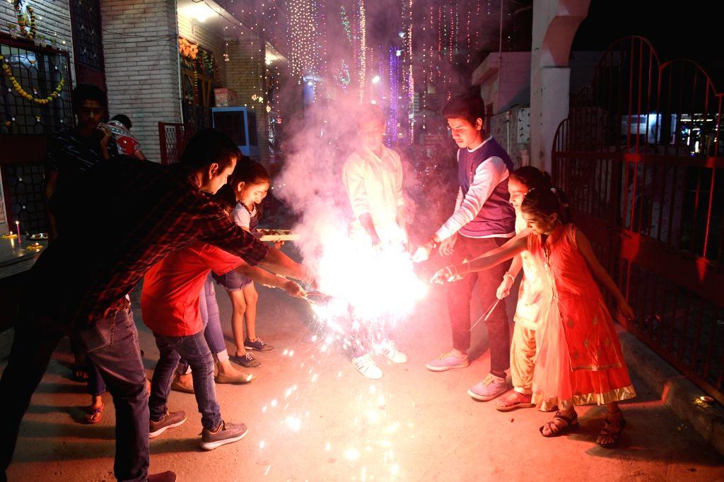 People burn crackers to celebrate Diwali at Noida, Uttar Pradesh on oct. 27, 2019.