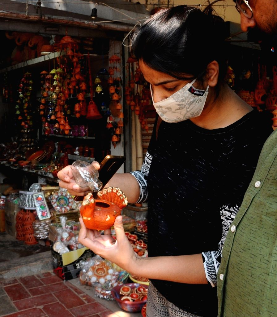 People busy shopping for earthen lamps ahead of Diwali celebrations, in New Delhi on Oct 30, 2020.