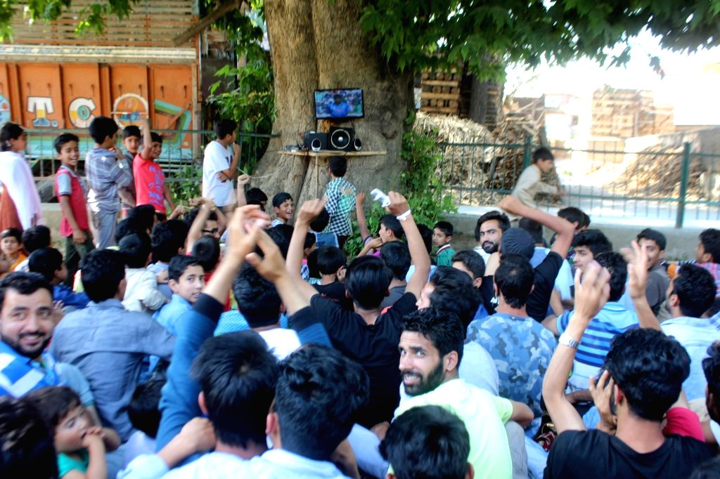 People busy watching ICC Champions Trophy Final match between India and Pakistan that is being played in London's Kennington Oval; in Anantnag on June 18, 2017.