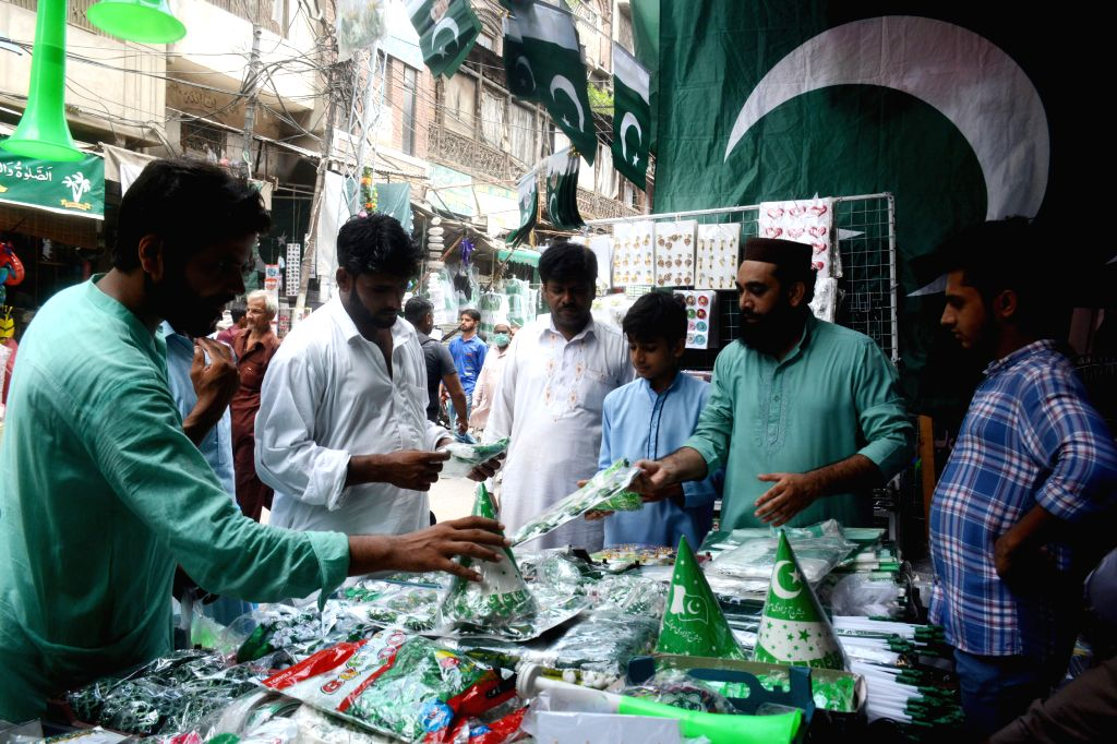 People buy festive decorations at a market on the eve of the Independence Day in Lahore, Pakistan, on Aug. 13, 2020.