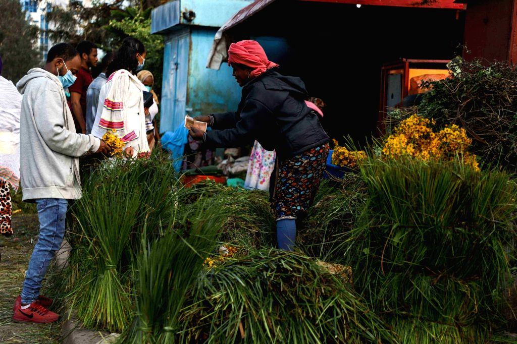 People buy freshly-collected grass and golden daisies ahead of the Ethiopian New Year in Addis Ababa, capital of Ethiopia, on Sept. 10, 2020. Ethiopians on ...