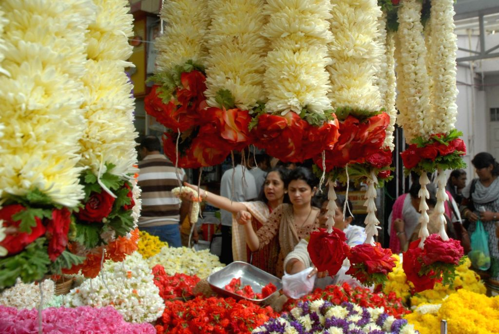 People buying flowers for the tomorrows Karnataka traditional festival `Varamahalakshmi` fest in Bangalore on August 15, 2013. (Photo::: IANS)