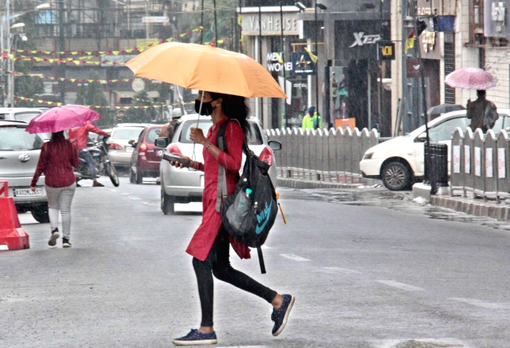 People carry umbrellas to shield themselves during rains triggered due to the effect of cyclonic storm Nivar, on Nov 26, 2020.