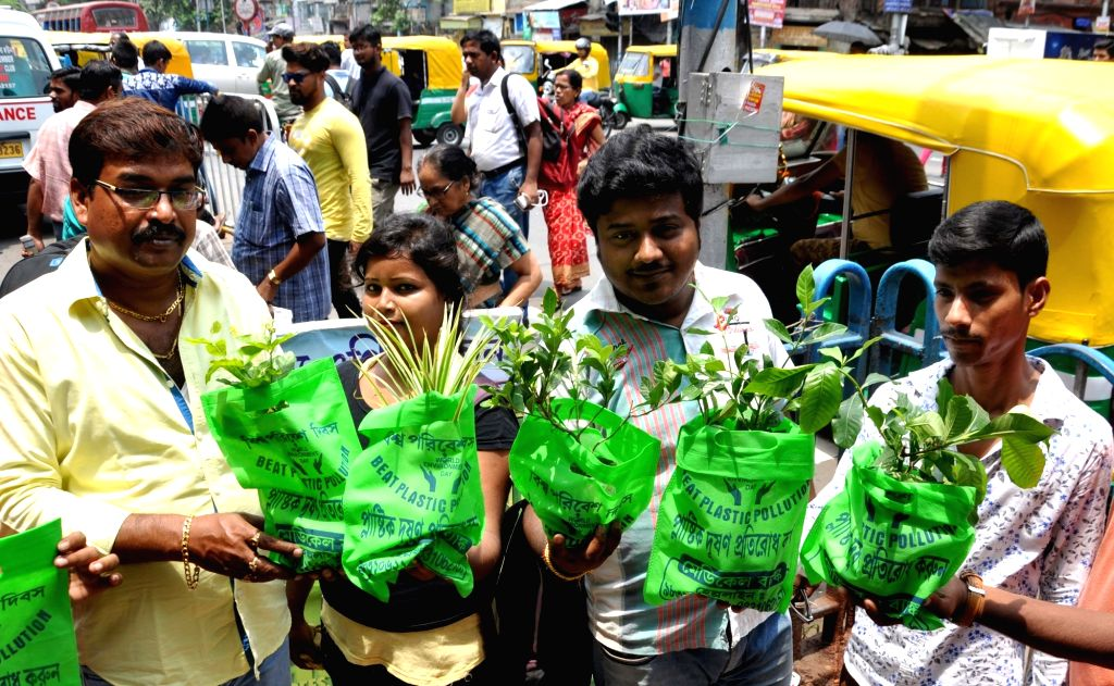 People carrying plant saplings participate in a rally to spread awareness about plastic pollution on the occasion of World Environment Day, in Kolkata on June 5, 2018. June 5 is observed as ...