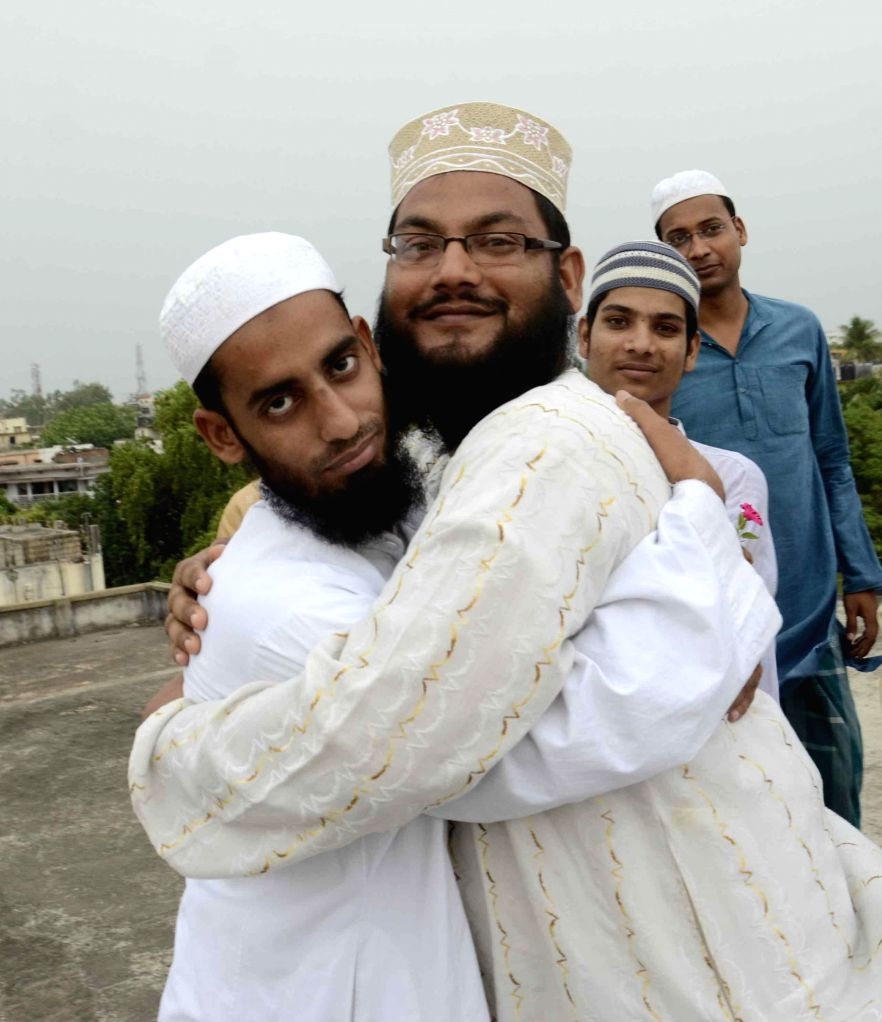 People celebrate after sighting of the sliver of a new moon which marks the beginning of holy month of Ramadan in Patna on June 29, 2014.